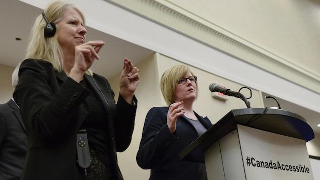 La ministre Carla Qualtrough est accompagnée d'une interprète qui traduit ses propos en langue des signes.