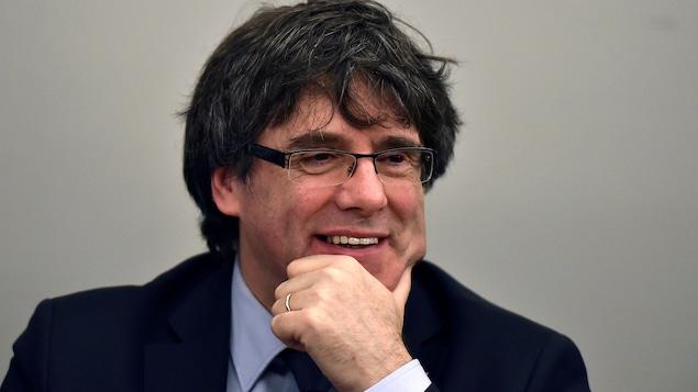 Carles Puigdemont la main au menton, esquissant un sourire.
