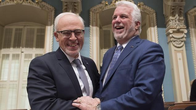 Carlos Leitao et Philippe Couillard se serrent la main en riant à l'Assemblée nationale.