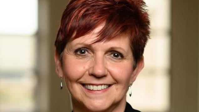 Une femme souriante aux cheveux courts portant un veston avec un collier et boucles d'oreilles longues