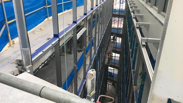 Des ouvriers travaillent sur une nacelle, suspendue entre les étages.