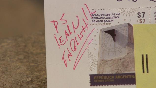 Photo de la carte postale, où quelqu'un a écrit à l'encre rouge « apprenez l'anglais ».