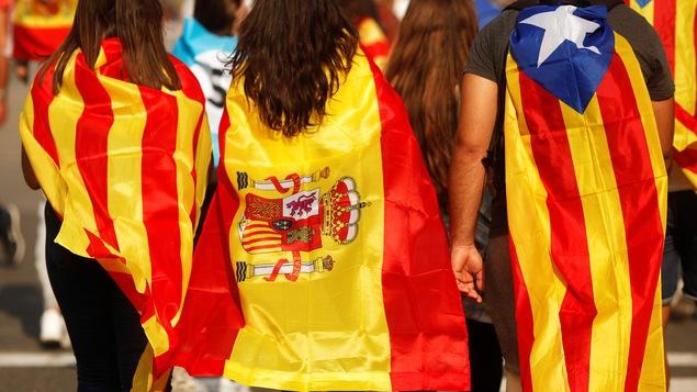 Des jeunes enveloppés dans des drapeaux catalan, espagnol et indépendantiste catalan, lors d'une manifestation à Barcelone, le 3 octobre.