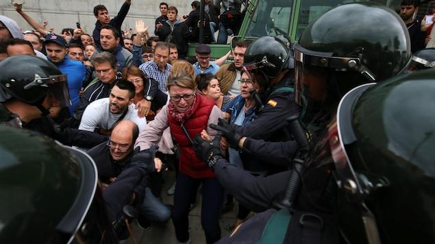Des agents de la Garde civile espagnole tentent de déloger des Catalans désirant participer au référendum sur l'indépendance.