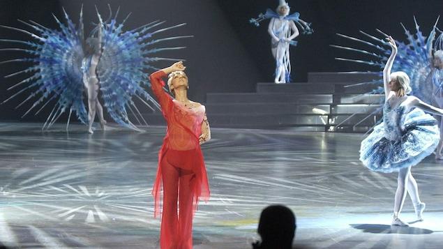 Habillée en rouge, la chanteuse est accompagnée de danseurs sur la scène.