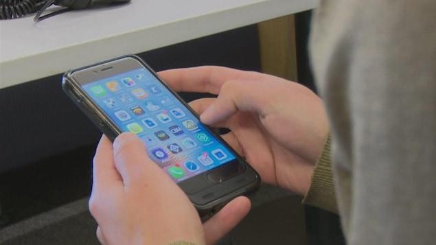 Image rapprochée des mains d'une personne tenant son téléphone intelligent.