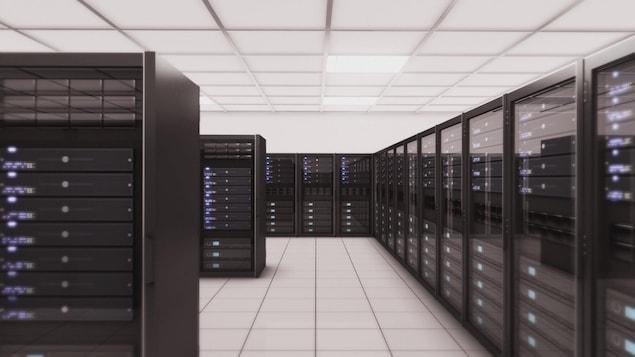 On voit des centaines de serveurs informatiques empilés les uns sur les autres et disposés en rangées.
