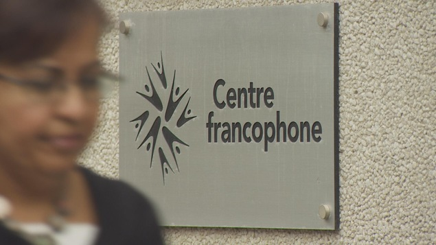Photo d'une femme qui passe devant le panneau d'entrée du Centre francophone de Toronto.