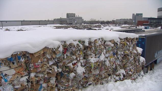 Des ballots de matières recyclables dans la neige, près du même centre, à Montréal, en janvier 2018 derrière des camions