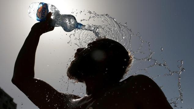 Un homme se rafraîchissant avec une bouteille d'eau