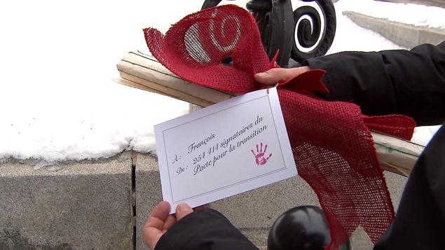Des mains tiennent un rouleau de papier orné d'un ruban rouge et une carte disant « À François, de 254 414 signataires du Pacte pour la transition ».