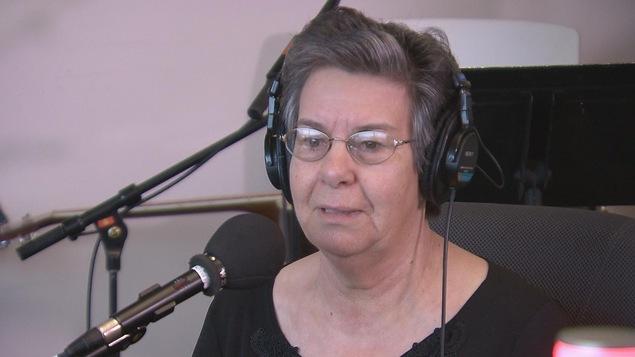 Une femme coiffée d'écouteurs devant un micro