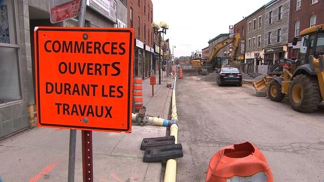 Chantier sur la rue Notre-Dame Ouest, avec une pancarte indiquant que les commerces sont ouverts