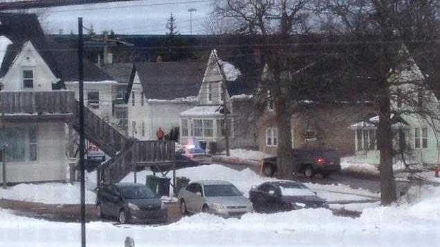 Des policiers devant une maison en ville