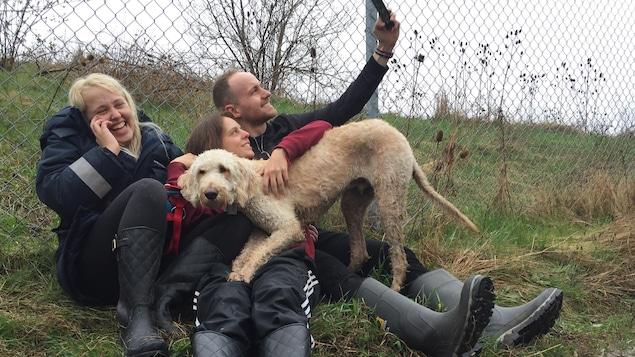 Trois personnes jouent avec un chien.