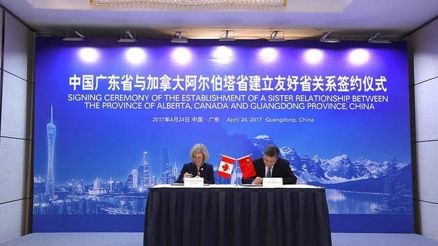 La première ministre albertaine, Rachel Notley, signe l'accord de relation commerciale entre sa province et celle du Guangdong, en présence du gouverneur de la province chinoise, Ma Xingrui.
