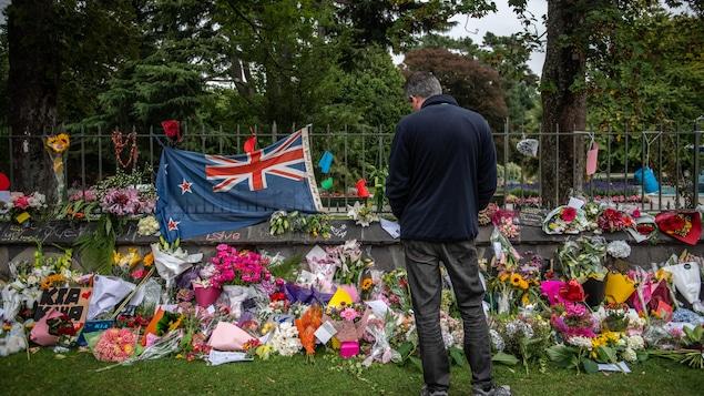 Un homme se recueille devant des fleurs et un drapeau de la Nouvelle-Zélande, déposés sur le mur d'un parc.
