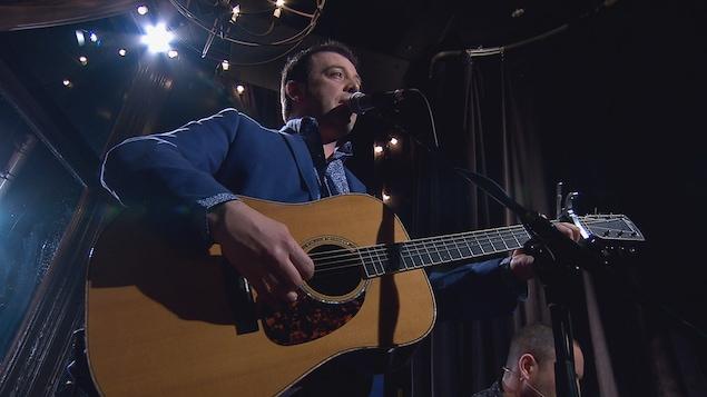 Le chanteur Christian Kit Goguen avec sa guitare.