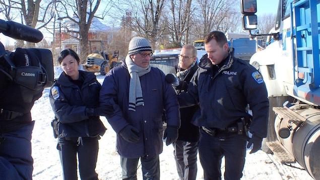 M. Picard, escorté par deux policiers de la RIPRSL.