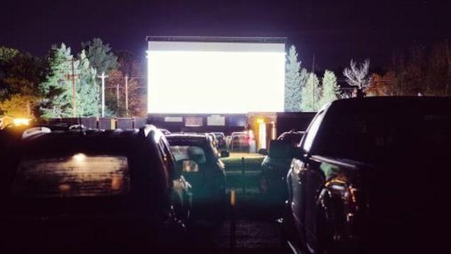 Des voitures sont stationnées devant un écran géant en pleine nature.