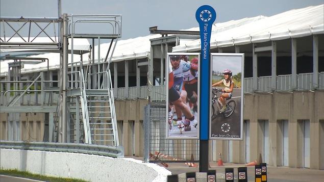 Des affiches montrant une cycliste et des patineurs au circuit Gilles-Villeneuve de l'île Notre-Dame, au parc Jean-Drapeau