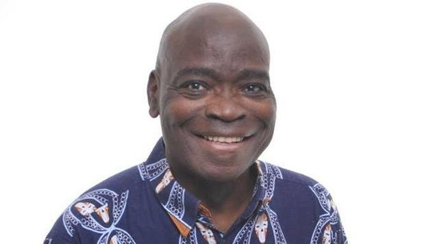 Un homme noir sourit à la caméra lors d'une prise de photo officielle.