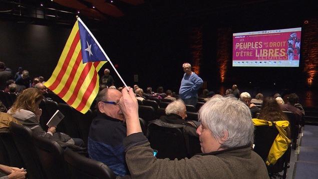 Une personne assise dans un auditorium agite un petit drapeau catalan, tandis que le slogan « Les peuples ont le droit d'être libres » est affiché sur un écran au-dessus de la scène.