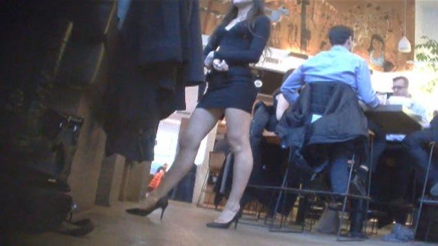 Une serveuse dans un bar qui porte une jupe courte.