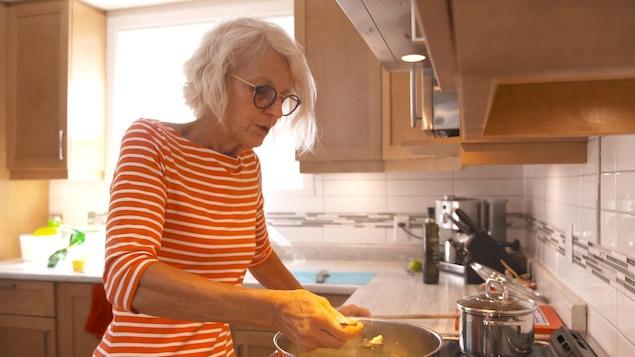 Une dame de plus de 60 ans cuisine.