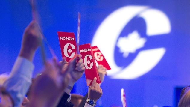 Des personnes assise dans une grande salle, vues de profil. votent en tenant des cartons en l'air.