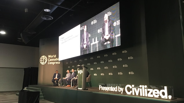 Cinq hommes sont assis sur une scène et discutent alors qu'un écran géant au-dessus d'eux diffuse la conférence pour le public.