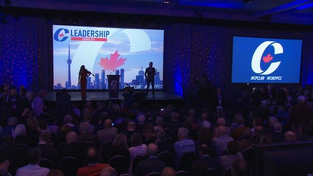Des personnes sont sur scène devant une projection où l'on peut voir le logo du Parti conservateur du Canada (un « C » entourant une feuille d'érable rouge). Une petite foule les regarde.