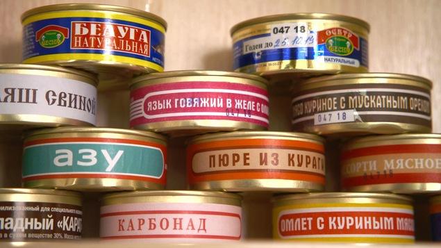 On voit en gros plan des conserves qui portent des inscriptions en russe.