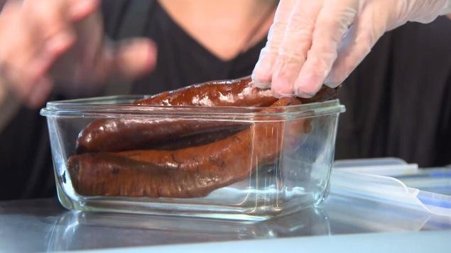 Un commis met des saucisses dans le contenant en verre du client.