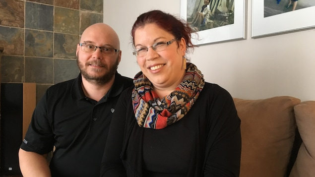 Un couple sourit à la caméra, assis sur un divan.