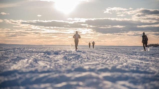 Un homme court sur la neige.