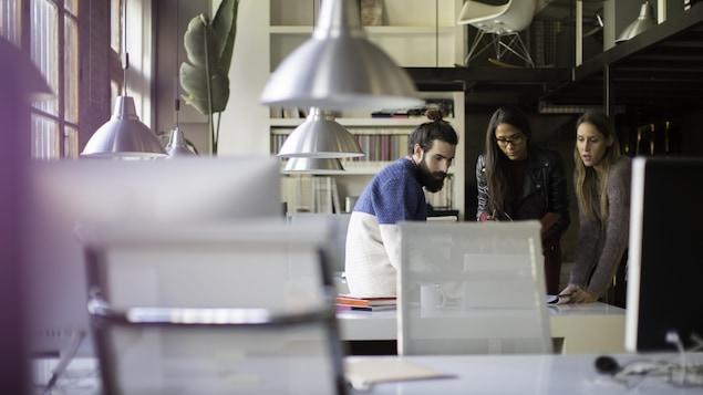 Trois personnes travaillent ensemble dans un espace collaboratif.