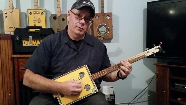 Todd Creamer joue d'une guitare en boîte à cigare