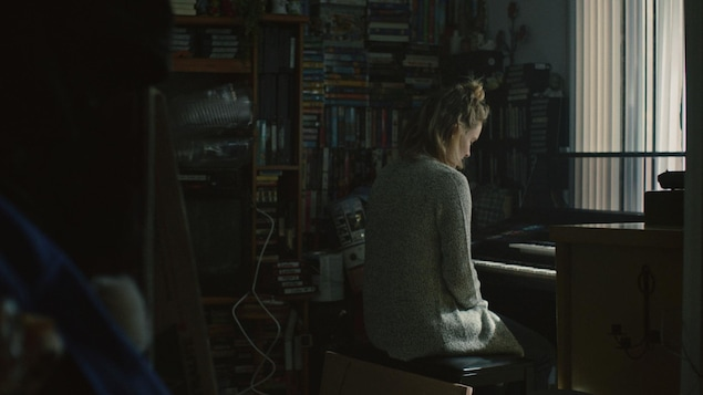 Une femme devant une mur de disques. Elle est assise devant un clavier pour jouer de la musique.