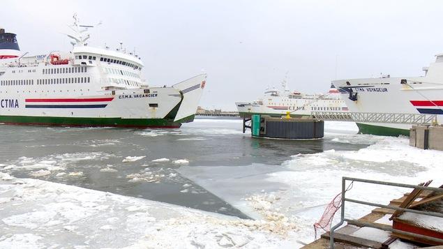 Trois navires dans un port de mer.