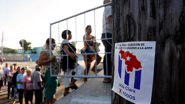 Des hommes et des femmes sont photographiés en file, lors d'une journée ensoleillée. Ils sont légèrement flous, puisque le focus de la caméra est effectué sur une petite affiche en avant-plan qui dit, en espagnol, « 11 mars, élection des députés et des délégués à la APPP ».