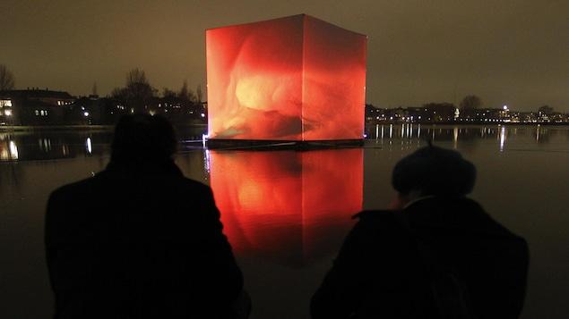 Deux personnes regardent une étendue d'eau sur laquelle flotte un énorme cube illuminé.