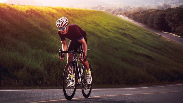 Un cycliste en train de monter une pente asphaltée sur son vélo. En arrière-plan, on aperçoit un talus gazonné et des montagnes couvertes de feuillus.