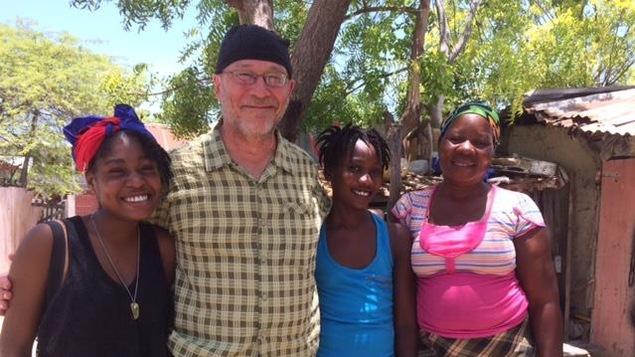 Trois femmes et un homme sont côte à côte et prennent la pose. Ils se trouvent en Haïti.