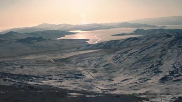 Cette image extraite de la bande annonce du film Dans les forêts de Sibérie montre le lac Baïkal de loin avec des montagnes.