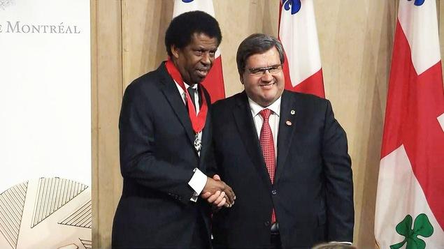 L'écrivain Dany Laferrière serre la main du maire de Montréal Denis Coderre après avoir été fait officier de l'Ordre de Montréal, mercredi.
