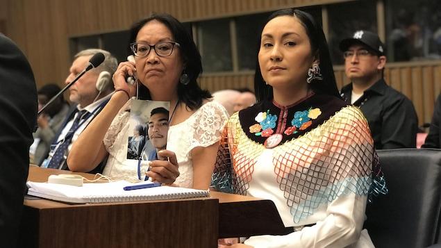 La mère et la cousine de Colten Boushie assises dans l'assemblée des Nations unies, montrant une photo de Colten Boushie.