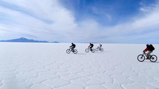 Des cyclistes roulent sur une surface couverte de sel s'étendant à perte de vue.