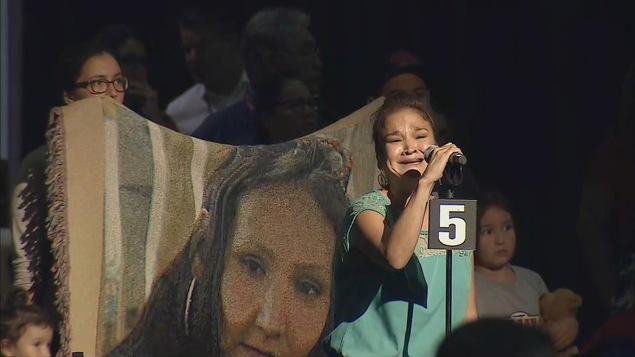Delores Stevenson tient le micro en train de pleurer. Derrière elle se trouve une femme tenant une toile sur laquelle on voit la photo de sa nièce disparue.