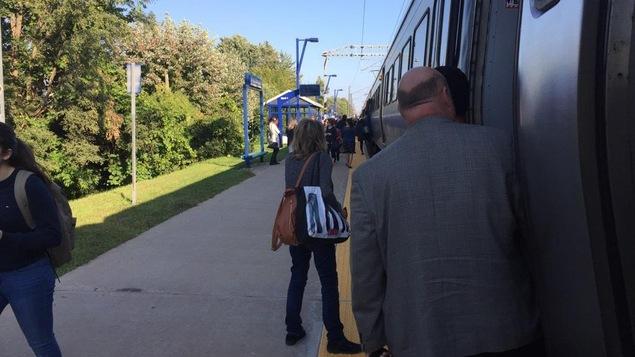 Une femme et un homme, en avant-plan, sont photographiés en train de descendre d'un train de banlieue.